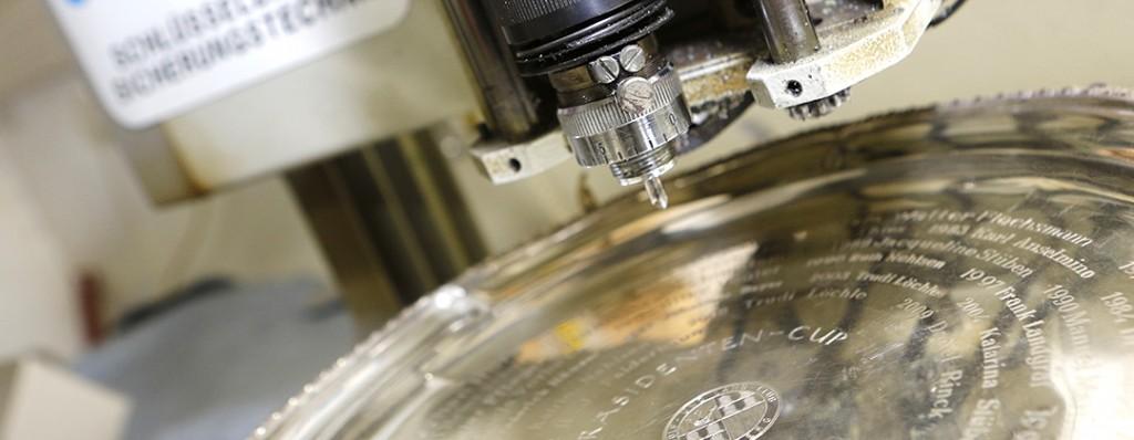 Ein rundes Schild wird auf einer Graviermaschine graviert